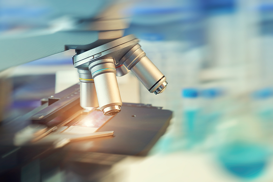 Scientific background with closeup on light microscope and blurred laboratory